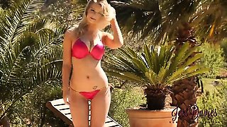 Jess Davies strips from red bikini by the pool.