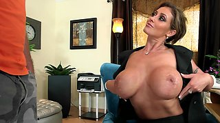 A hot mature bimbo reveals her big tits in the office to fuck the guy