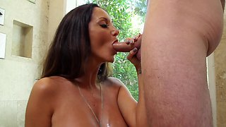 A bimbo with huge tits is placing soap over her sexy flesh