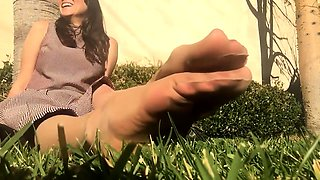 Pantyhosed brunette flaunts her sexy feet in the outdoors